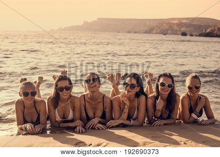 Stunning girls lying on the sand at the seaside
