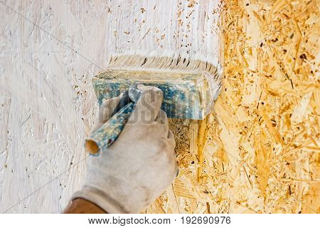 A man paints a wall using a brush. Painting with white paint. The hand in the glove uses a brush with white paint.