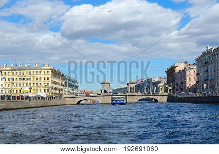 SAINT PETERSBURG RUSSIA - MAY 3 2017: View of Lomonosov Bridge across Fontanka River. Unknown people walk along street St. Petersburg Russia