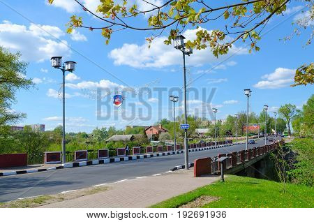 POLOTSK BELARUS - MAY 19 2017: Unknown people walk along Red Bridge across Polota River (monument of Patriotic War of 1812 on Polotchyna) Polotsk Belarus