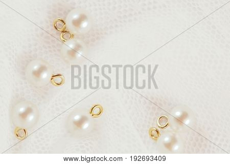 Closeup of pearl buttons on white wedding lace