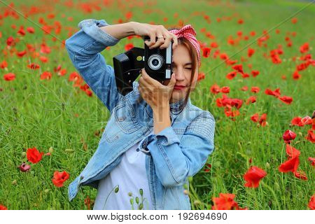girl with retro camera in a field of poppies.