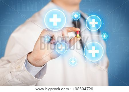 A male doctor in coat in front of a blue wall holding a pill between his fingers with lines and white crosses in circles