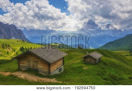 Scenic view of traditional wooden alpine huts on a green grassy meadow in alpine valley Dolomites Italy