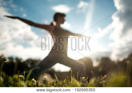 Yoga outdoors. Sporty fit caucasian woman doing Ashtanga Vinyasa Yoga asana Virabhadrasana 2 Warrior pose posture in nature. Blurred view.