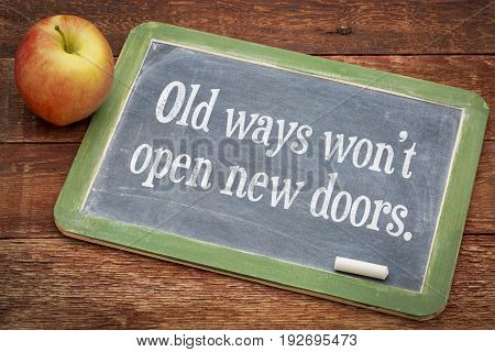 Old ways do not open new doors - motivational concept on a slate blackboard against red rustic barn wood