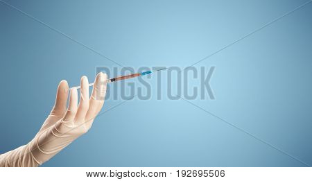 Female doctor hand holding syringe with blue background