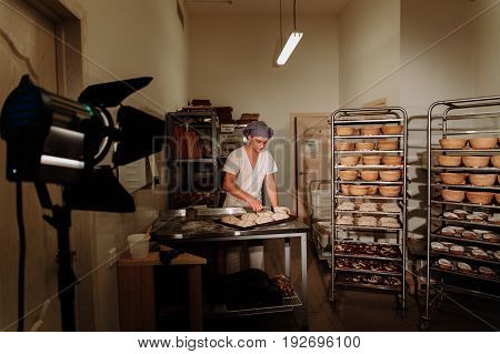 Baker kneading dough and forming loaf of bread, a Baker makes manual incisions on the dough for the bread