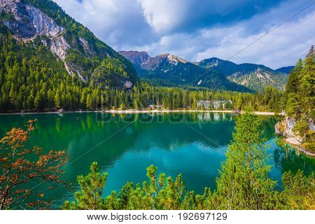 Green water reflects the surrounding mountains and forest. Magnificent lake Lago di Braies. South Tyrol, Italy. The concept of walking and eco-tourism