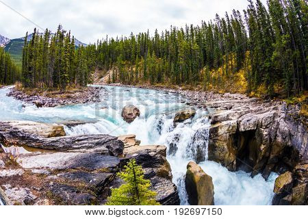 Autumn trip to Canada. Small island in the river. Sanvapta Great Falls in Jasper National Park. The concept of extreme and ecological tourism