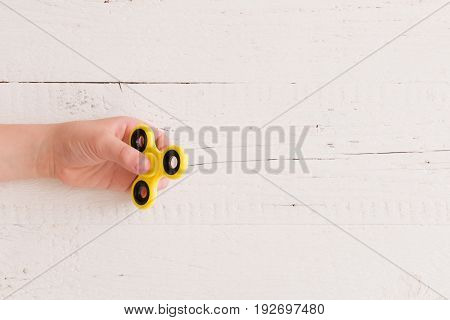 Child's hand spinning a fidget spinner device. Top view. Playing with a yellow hand spinner fidget toy