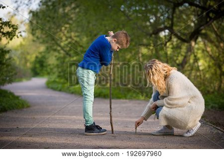 Portrait of woman and kid boy drawing on the ground in the park. Mother and child playing game outdoors. Together. lifestyle