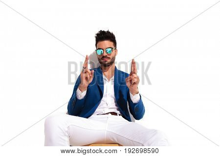 young elegant man sitting and holding fingers crossed on white background