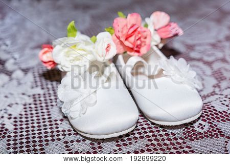 Pair of white baby shoes on pants and shirt at Christening Baptism Ceremony at church