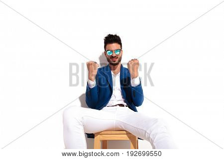 serious elegant man sitting and showing his fists as in he is ready for a fight and win on white background