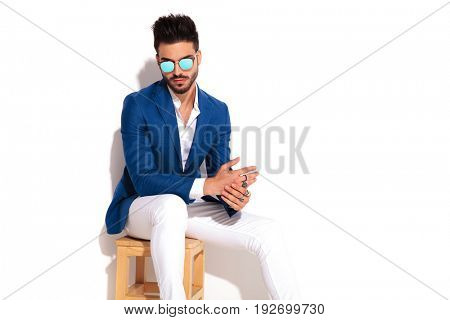 elegant man wearing sunglasses sitting on chair and rubbing his palms together on white background
