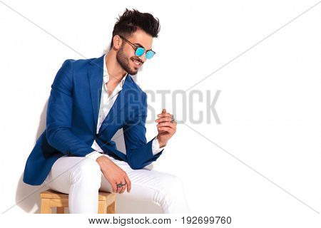 side view of a laughing elegant young man wearing sunglasses on white background