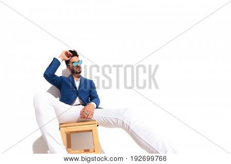 seated sexy man with hand on forehead dreaming away on white background