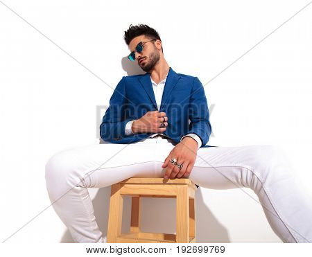 tired elegant man wearing sunglasses is sitting on chair and holds the coat's button or collar on white background