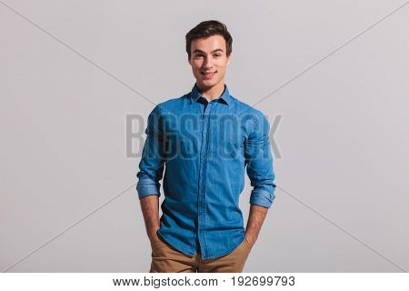 relaxed casual man standing with hands in pockets on grey background