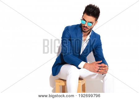 elegant man holding palms together while sitting on chair and looks down on white background