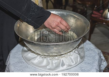 The priest blesses Christening Baptismal Font filled with Holy Water at the church during the ceremony at Burgas