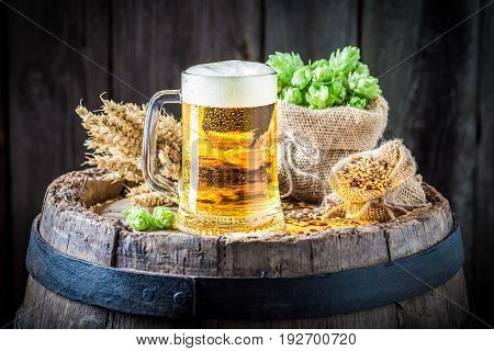 Cold Beer With Foam, Wheat And Hops On Old Barrel