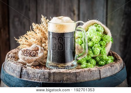Pint Of Dark Beer With Wheat And Hops On Barrel