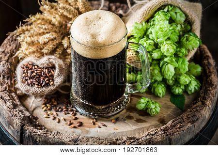 Dark Beer With Foam, Wheat And Hops On Oak Barrel