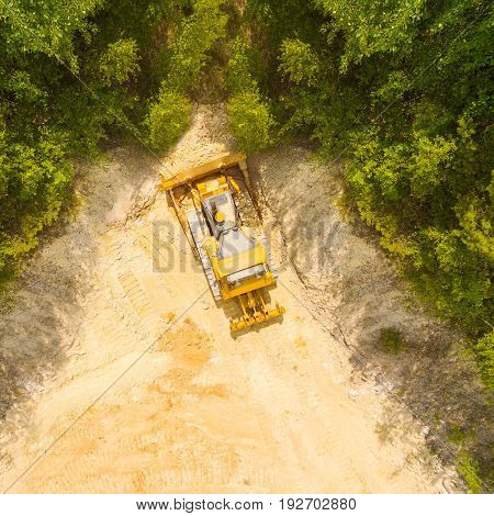 Deforestation of construction site. Aerial view to bulldozer working in forest. Heavy industry from above.
