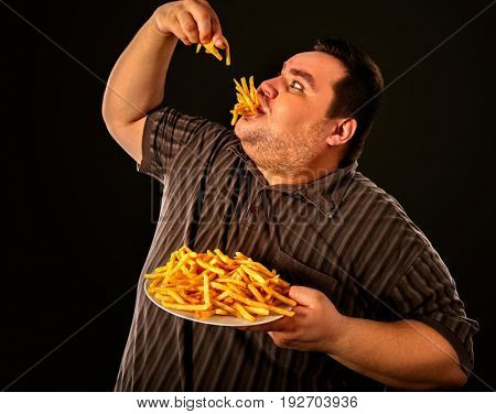 Diet failure of fat man eating fast food . Overweight person who spoiled healthy food by eating french fries. Junk meal leads to obesity. Foods high in fat concept.