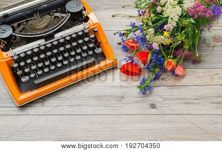 Workspace with orange vintage typewriter with a bouquet of summer field flowers on a gray background.