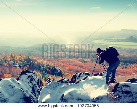 Professional On Cliff. Nature Photographer Takes Photos With Mirror Camera On Snowy Rock.