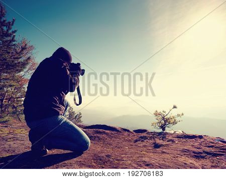 Photographer  Look Down Into Fogy Valley. Man Is Kneeling On Cliff And Takes Photos.