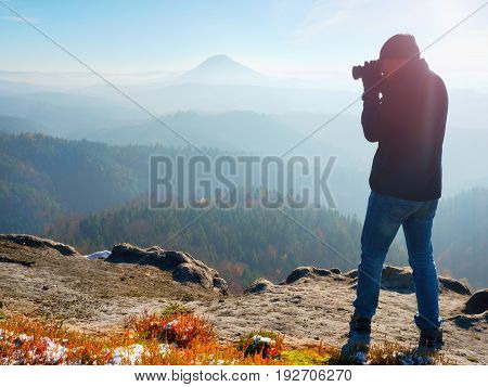 Professional Photographer Takes Photos With Mirror Camera On Peak Of Rock. Dreamy Fog