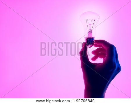 Female hand and holding luminous light bulb. Electric incandescent light bulb in hand on purple background. Inspiration Ideas concept.