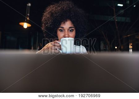 Beautiful woman working late at night in office. African female entrepreneur drinking coffee and looking at laptop computer.