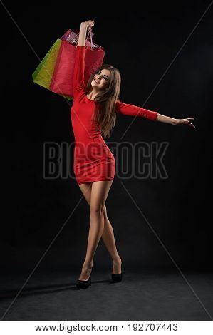 Vertical studio shot of a gorgeous happy woman wearing sexy red dress walking with her shopping bags on black background shopaholic happiness leisure activity buying consumer purchase concept.