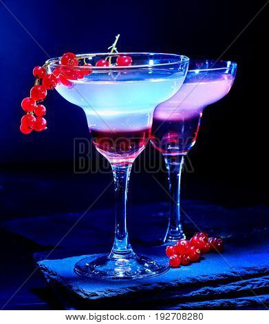 Nonalcoholic drink cherry in cocktail glass on black background. Group nonalcoholic beverage decorated with twig red red currant.