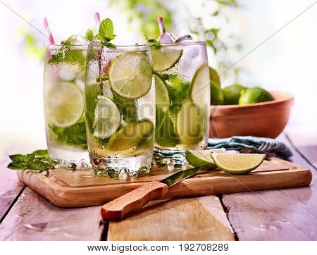 Cold water with lemon and mint leaf. Fresh lemonade with lime slice and ice cubes. Nonalcoholic beverage in cocktail glass with cocktail straw on wooden board. Table setting in rural style.