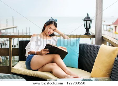 Girl Reading Book On The Balcony With Seaside View