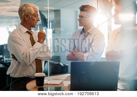 Shot of senior boss giving business instructions to man standing near by. Corporate professionals having standing meeting in modern office.