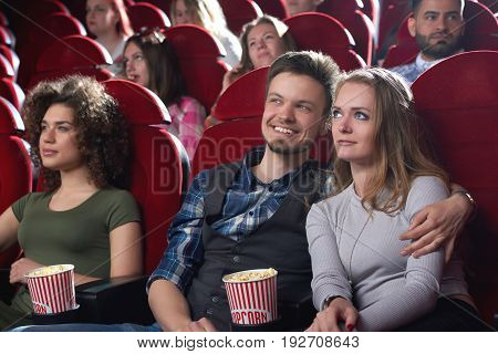 Handsome young man embracing his beautiful girlfriend while watching a movie together at the cinema people lifestyle romance dating relationships entertainment cuddling hugging romantic.