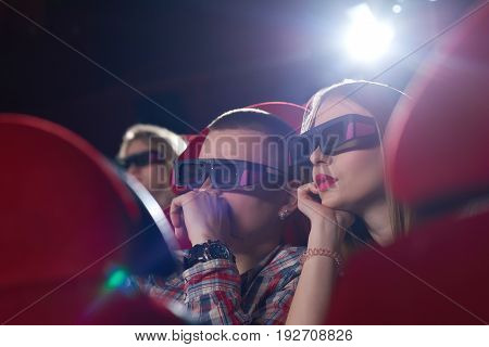 Close up shot of a young couple wearing 3D glasses watching a movie at the local cinema technology modern realistic entertainment activity concept.