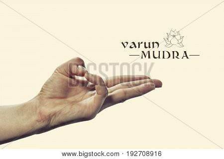 Varun mudra. Yogic hand gesture. Isolated on toned background.
