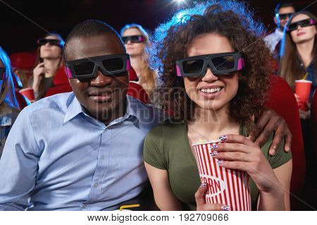 Happy young African man embracing his beautiful cheerful girlfriend while enjoying watching a 3D movie at the cinema together eating popcorn relationships dating people leisure technology modern.