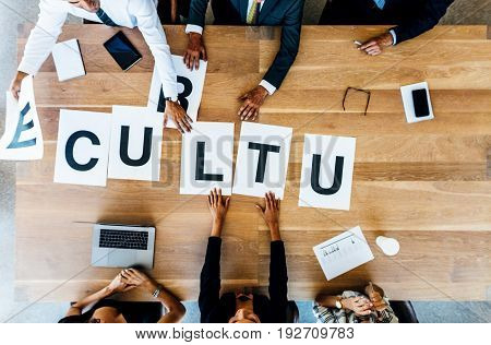 Top view of business group placing the word sign Culture on table. Business people meeting and discussing over work culture in office.