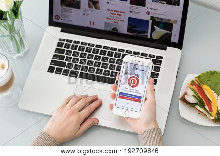 Alushta Russia - May 26 2017: Woman hand holding iPhone with social Internet service Pinterest on the screen. iPhone was created and developed by the Apple inc.