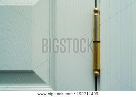 Close-up new modern door hinge on wooden door.