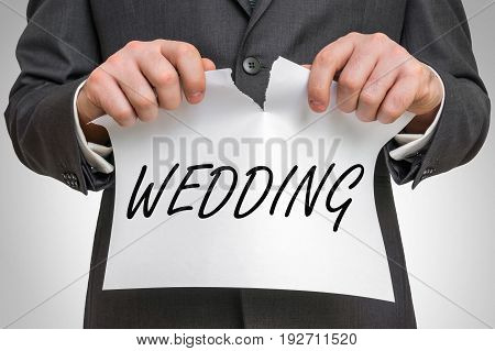 Businessman Tearing Paper With Wedding Word